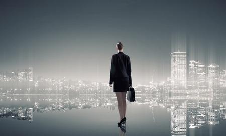 lider: Empresaria de pie con la espalda contra la vista panorámica nocturna de la ciudad