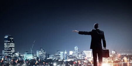 oration: Rear view of businessman against night city gesturing with hand