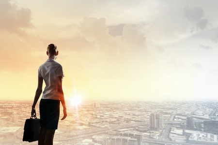 new opportunity: Rear view of businesswoman look at sunrise above city Stock Photo