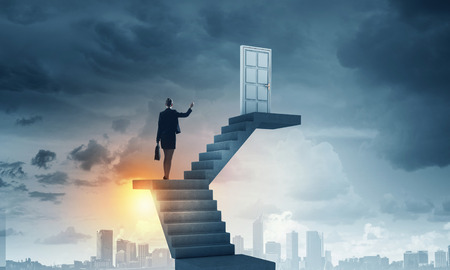 dream vision: Businesswoman walking up staircase to door in sky Stock Photo