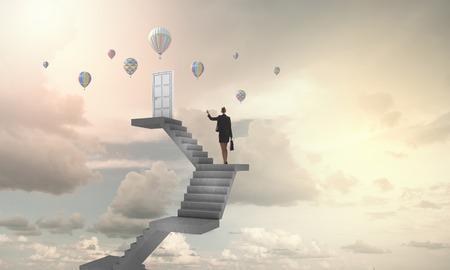Businesswoman walking up staircase to door in sky Stock Photo