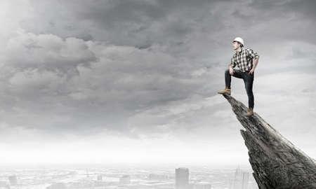 builder: Confidente joven constructor de pie en el borde de la roca por encima de la ciudad