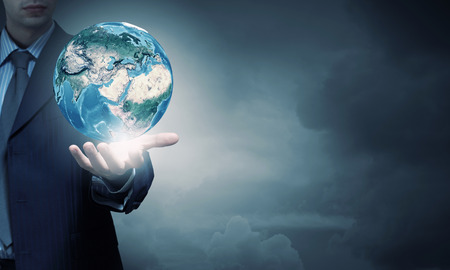 BUSINESSMEN: Hand of businessman holding earth planet. Stock Photo