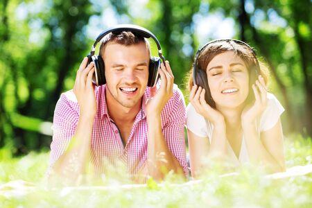 pareja enamorada: Amar a dos j�venes en la m�sica parque escucha verano Foto de archivo