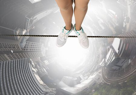 persona de pie: Top view of person standing on rope above city