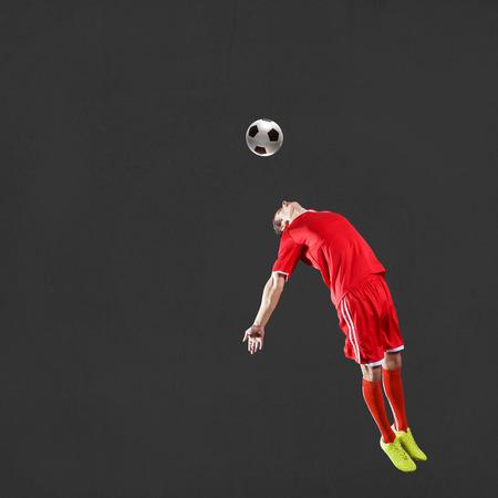 kicking ball: Soccer player kicking ball isolated over dark background