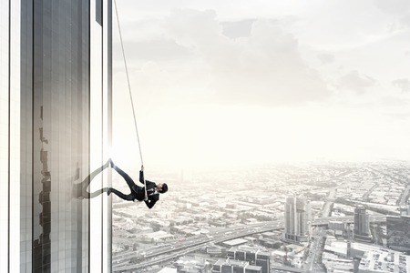 Concept of competition with businessman climbing office building with rope Banco de Imagens