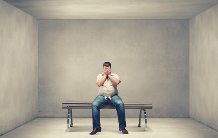 Fat man sitting on bench closing eyes with hands