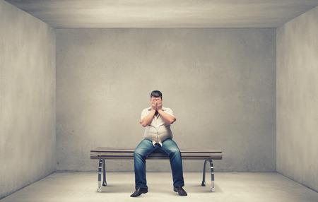Vet man zittend op de bank ogen sluiten met handen