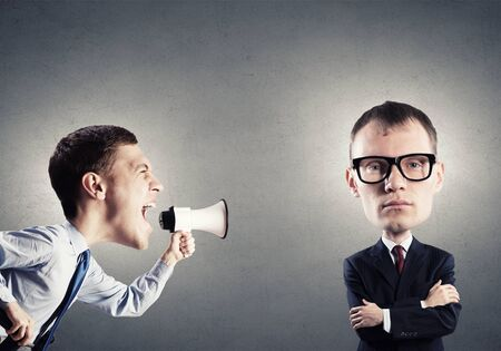 screaming: Funny young man with big head screaming emotionally in megaphone Stock Photo