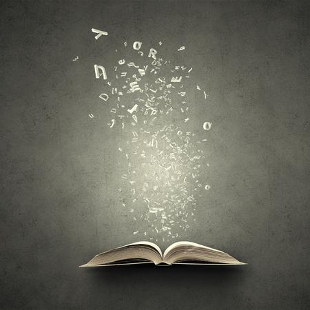 biblioteca: Viejo abrió libro con personajes volando de páginas Foto de archivo