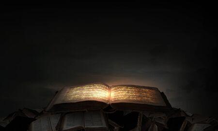 Antiguo libro mágico negro con luces en las páginas Foto de archivo - 42631820