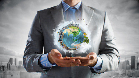 globe people: Young businessman holding Earth planet in hand.  Stock Photo