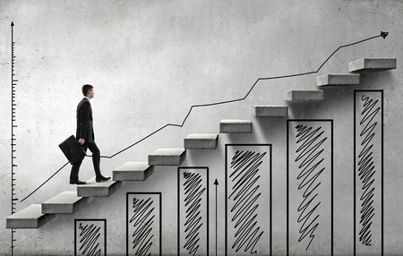 financial graph: Young businessman walking up on staircase representing success concept Stock Photo