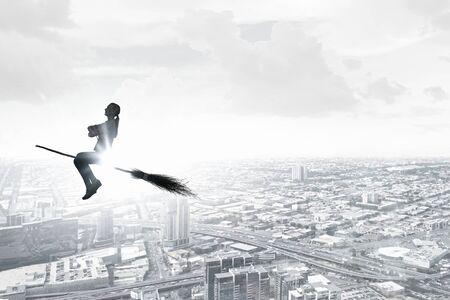 donna volante: Giovane donna felice che vola in cielo sulla scopa Archivio Fotografico