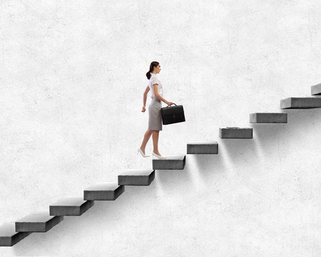 Young businesswoman walking up on staircase representing success concept Stock Photo