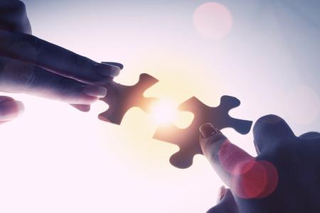 piezas de rompecabezas: Cerca de las manos de conexión elemento rompecabezas y hacer rompecabezas completo