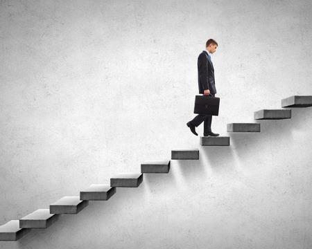 escaleras: Joven empresario caminando en la escalera que representa el concepto de éxito