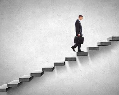 climbing ladder: Young businessman walking up on staircase representing success concept Stock Photo