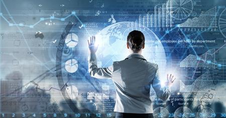 technologie: Vue arrière de la femme d'affaires travaillant avec les technologies virtuelles modernes