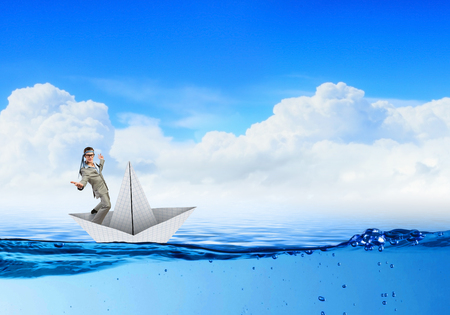 risky job: Businessman escapes from the crisis on a paper boat Stock Photo