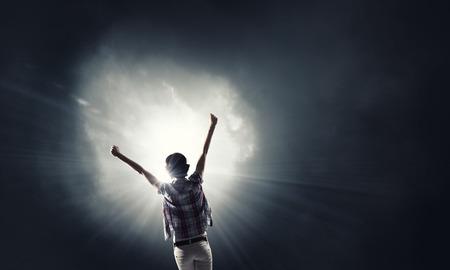 Achter mening van vrouw met handen omhoog geconfronteerd met succes Stockfoto