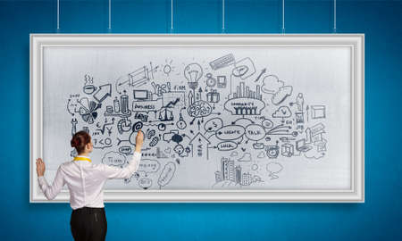 drawing a plan: Rear view of businesswoman drawing business plan on white banner