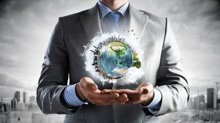Joven empresario sosteniendo el planeta Tierra en la mano.