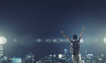 enjoyment: Rear view of young woman with hands up looking at night city