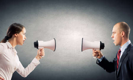 agression: Young furious people screaming agressively in megaphone Stock Photo
