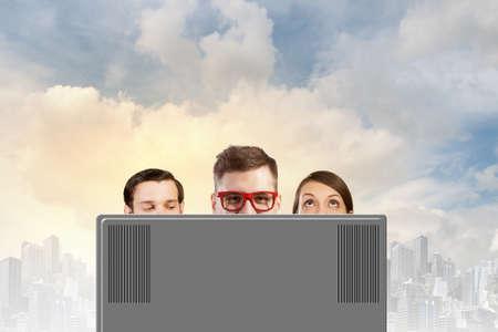 personas mirando: Gente joven que mira por encima del monitor del ordenador port�til Foto de archivo