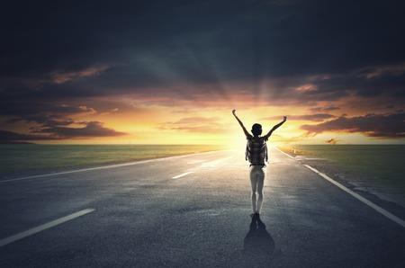 Achteraanzicht van het meisje met de handen omhoog gericht zonsopgang Stockfoto