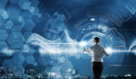 technik: Rückseitige Ansicht der Geschäftsfrau, die mit modernen virtuellen Technologien