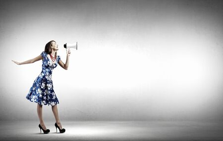 announcement message: Young woman making some announcement in trumpet Stock Photo