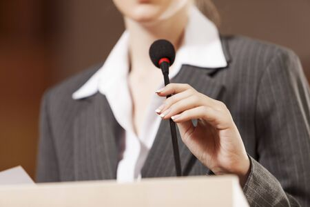 audience: Businesswoman standing on stage and reporting for audience Stock Photo