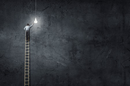 climbing ladder: Back view of businessman standing on ladder and reaching light bulb