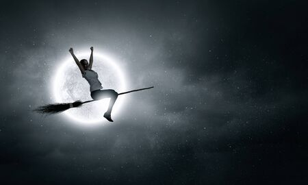 carelessness: Happy young woman flying in sky on broom