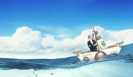 risky job: Businesswoman escapes from the crisis on a paper boat Stock Photo