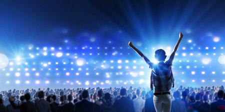 Vue arrière d'une jeune fille debout dans les lumières de scène