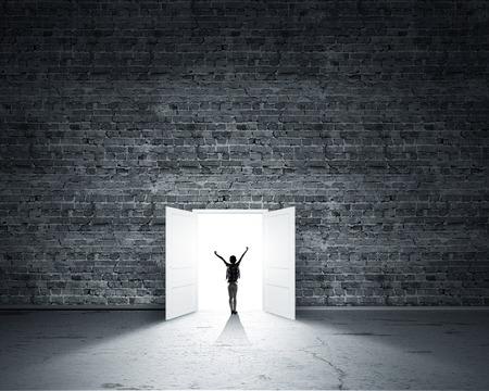 Achteraanzicht van de vrouw met de handen omhoog invoeren geopende deur