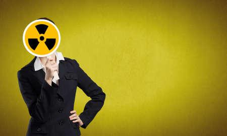 radiactividad: Empresaria irreconocible ocultando su rostro detr�s de signo radiactividad Foto de archivo