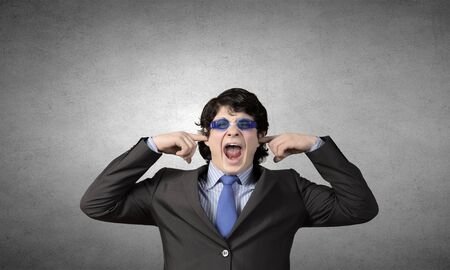 hands covering ears: Annoyed businessman covering his ears with his hands Stock Photo