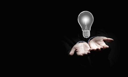 innovator: Close up of businessman holding symbol of  light bulb