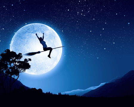 Young girl in casual flying on broom high in sky Stock Photo