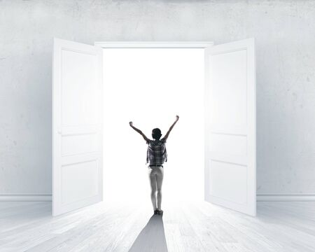 new opportunity: Rear view of woman with hands up entering opened door
