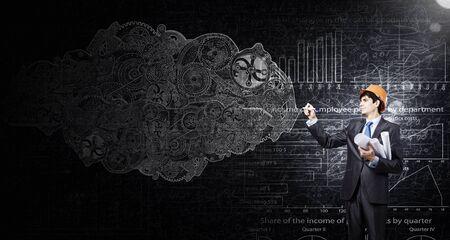 mur noir: Ing�nieur en casque dessin engrenages sur le mur noir