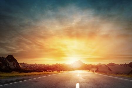 puesta de sol: Vaciar la carretera de asfalto y el sol naciente en el horizonte