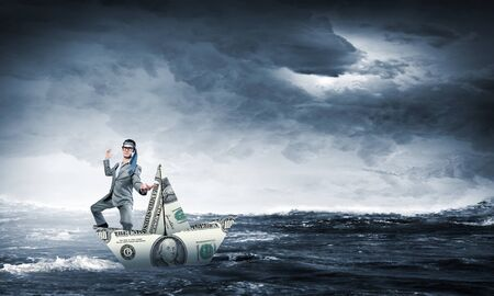 escapes: Businessman escapes from the crisis on a paper boat Stock Photo