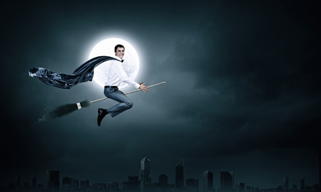 besom: Young businessman flying on broom high in sky