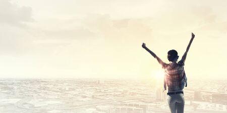mujer mirando el horizonte: Vista trasera de la muchacha con las manos en alto frente abone la salida del sol de la ciudad